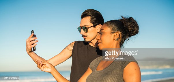 Young couple, Latino man and girl, take selfie on beach : Bildbanksbilder