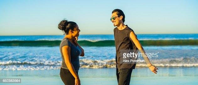 Young couple, Latino man and girl, talking on the beach : Stock Photo