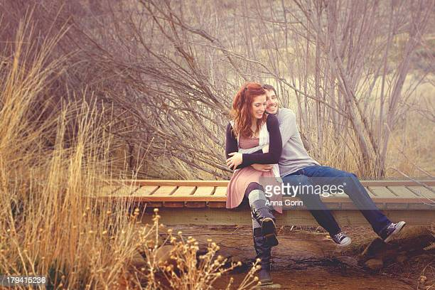 Young couple laugh together sitting on bridge