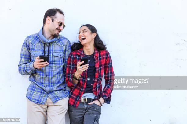 Young couple laughing and using smart phones on stree