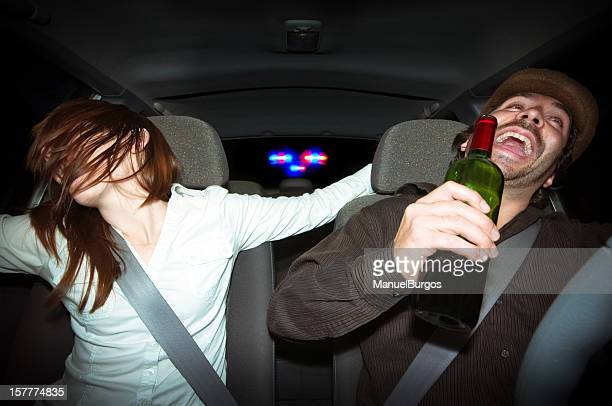 Young couple laughing in car while holding a bottle of wine
