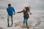 A young couple laugh, hold hands and paddle in the sea on Tynemouth beach in winter.