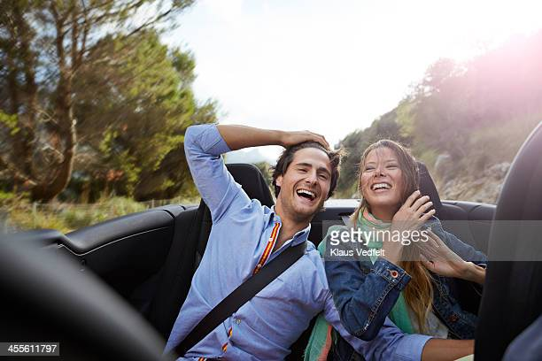 Young couple laughing on the backseat of car