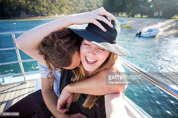 Young couple laughing taking selfie on boat deck in Sydney