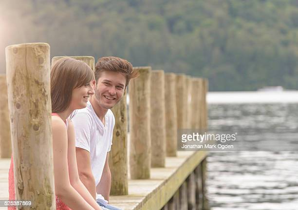 Young couple laughing together on jetty over lake