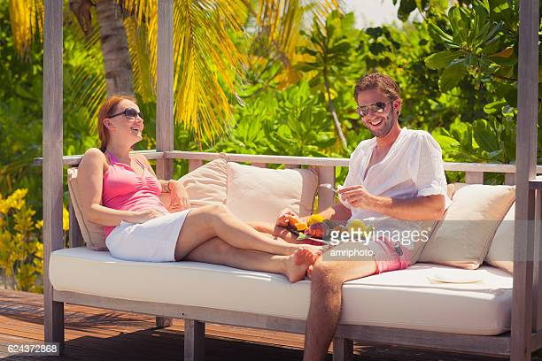 young couple laughing tropical island relax fruits