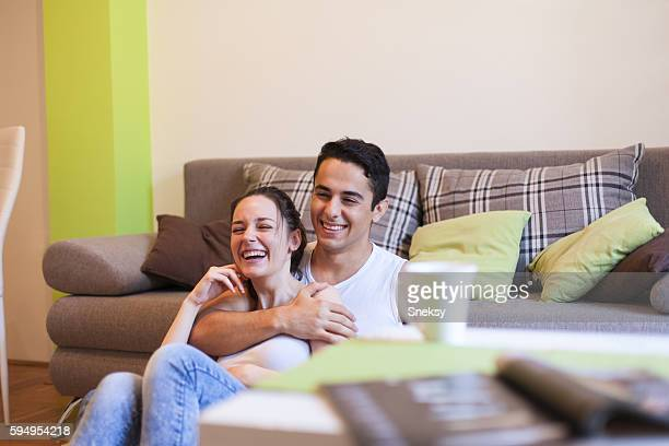 Young couple laughing watching movies at home.