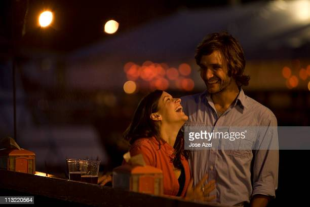 A young couple laughs and chats as they enjoy a beer on the deck of a local bar on the waterfront at Casco Bay Harbor in Portland, ME.
