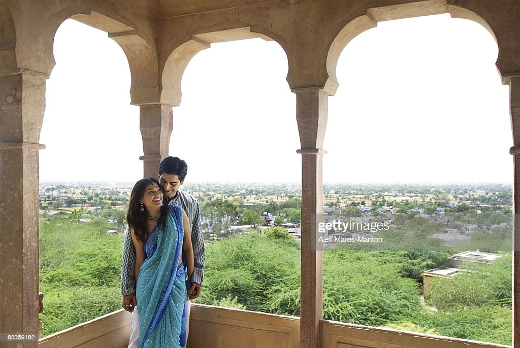young couple leaning against pillar on terrace balcony