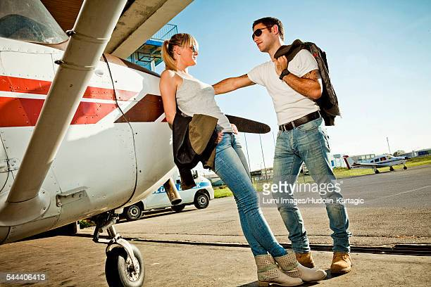 Young couple leaning against propeller airplane
