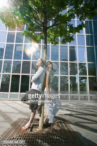 Young couple leaning against tree outside building, lensflare : Stock Photo