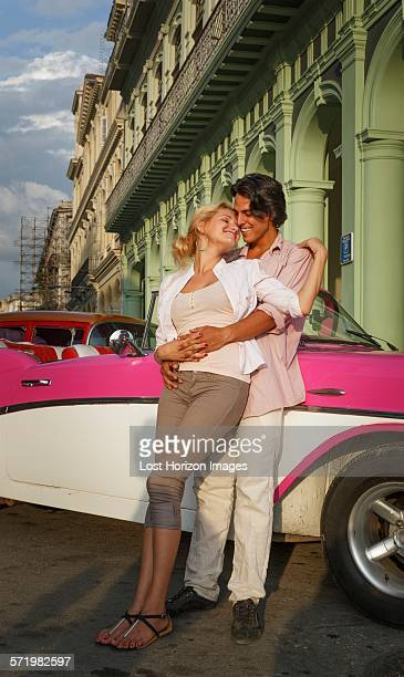 Young couple leaning against vintage convertible, Havana, Cuba