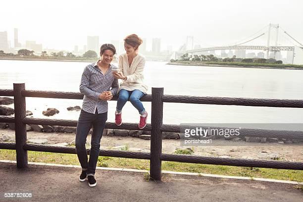Junges Paar Lehnend auf Zaun und mit Telefon