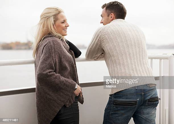 Young couple leaning on railing outdoors