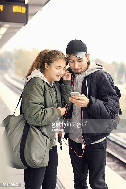 Young couple listening music through mobile phone on subway platform