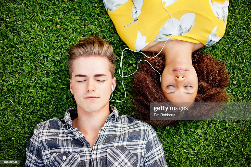 Young couple listening to and sharing music. : Stock Photo