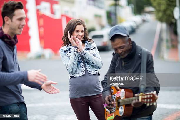 Young couple listening to guitar player on the street