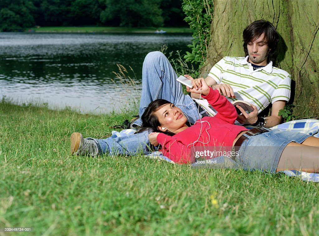 Young couple listening to mp3 player and reading by lake : Stock Photo