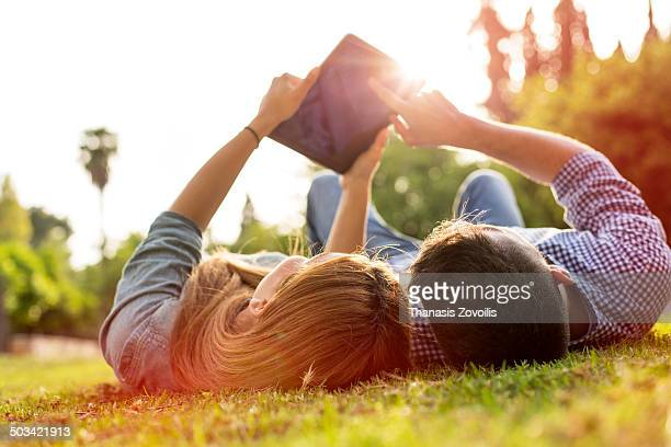 Young couple looking a tablet in a park