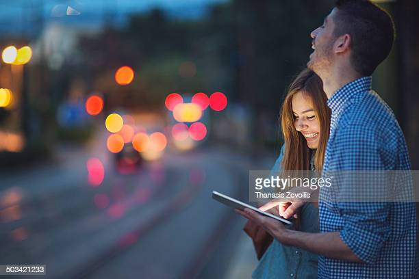 Young couple looking a tablet in the night