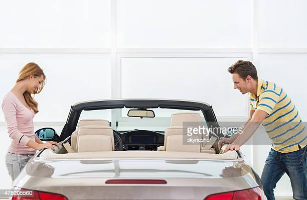 Giovane coppia guardando una nuova auto in un salone.
