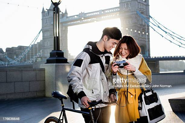 Young couple looking at camera at Tower Bridge, London, England