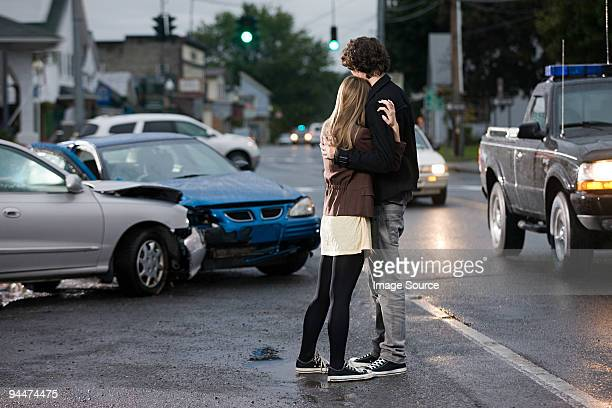 Young couple looking at crashed cars