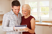 Young Couple Looking At Details For New Home