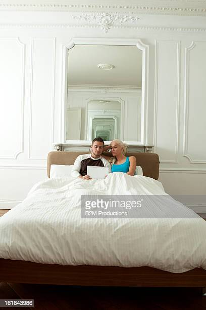 Young Couple Looking At Digital Tablet On Bed