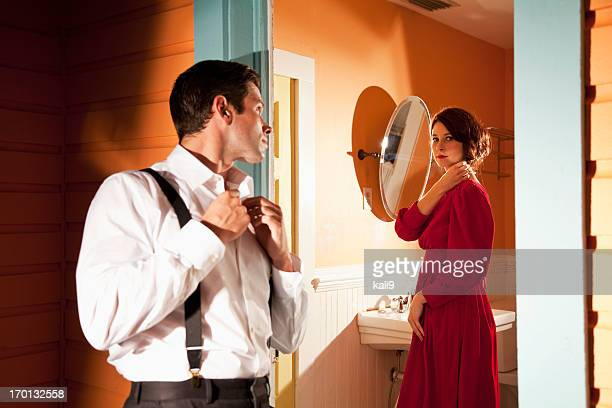 Young couple looking at each other through door