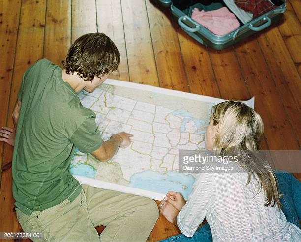 Young couple looking at map on floor, elevated view