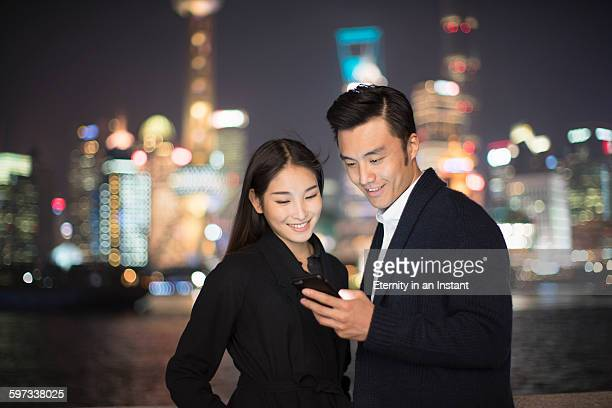 Young couple looking at phone in the city at night