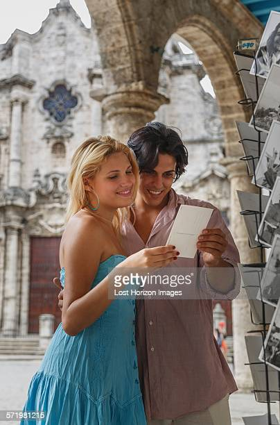 Young couple looking at postcards in the Plaza de la Cathedral of Havana, Cuba