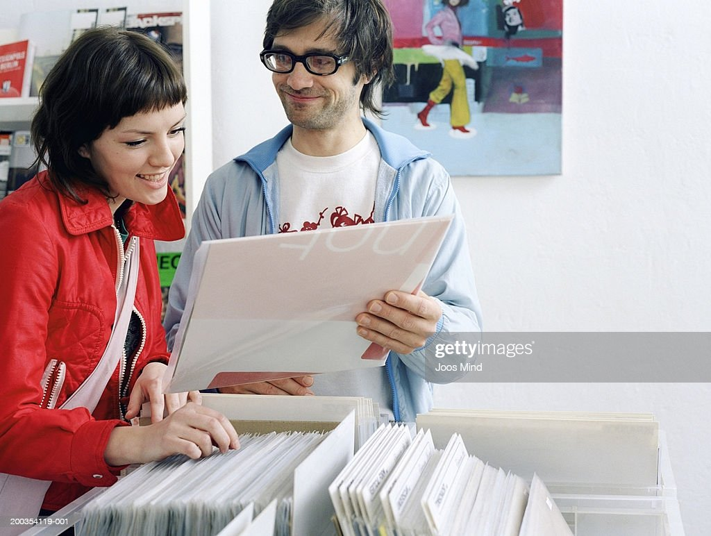 Young couple looking at records in record shop : Stock Photo