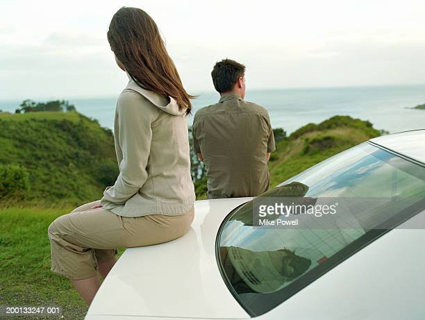Young couple looking at sea, woman sitting on trunk of car