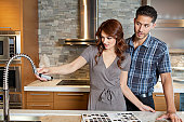 Young couple looking at sink faucet on kitchen counter in model home