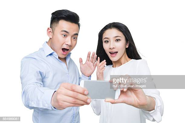 Young couple looking at smart phone with surprised expression