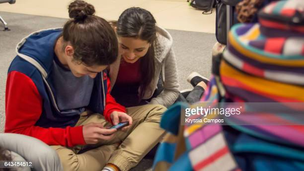 Young couple looking at smartphone at airport lounge