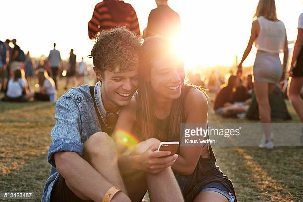 Young couple looking at smartphone & laughing