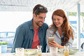 Young happy couple using mobile phone sitting at restaurant. Smiling casual man and beautiful woman with red hair looking at smartphone while enjoying lunch on terrace cafe. Portrait of mature couple