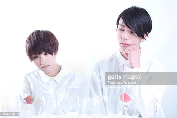 Young couple looking at strawberry in a glass