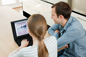 Young couple looking at travel insurance on laptop