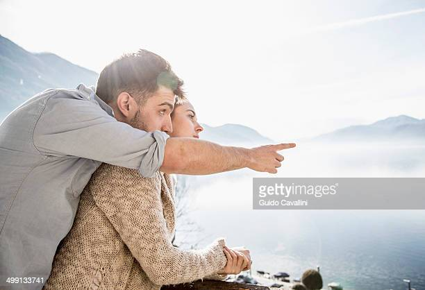 Young couple looking at view of lake and mountains