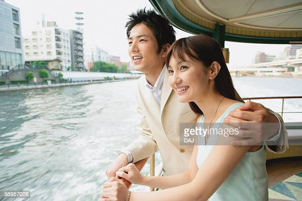 Young Couple Looking Cityscape From Ship