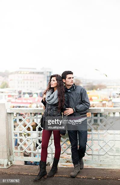 Young Couple Looking For Directions on a City Bridge