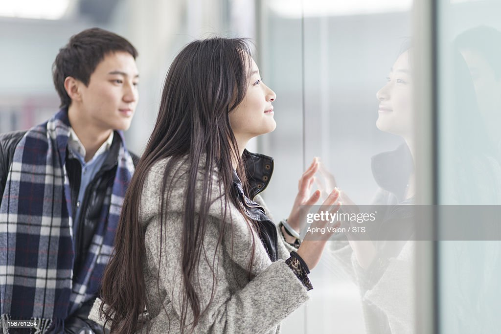 young couple looking into the shop window : Stock Photo