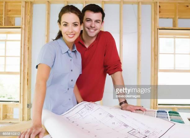 Junges Paar mit Blick auf Baupläne mit ihrem Haus im Bau im Hintergrund.