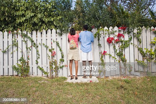 Young couple looking over white picket fence, rear view