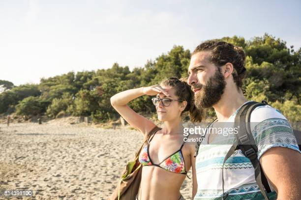 Young couple looking the horizon on a beach in Tuscany