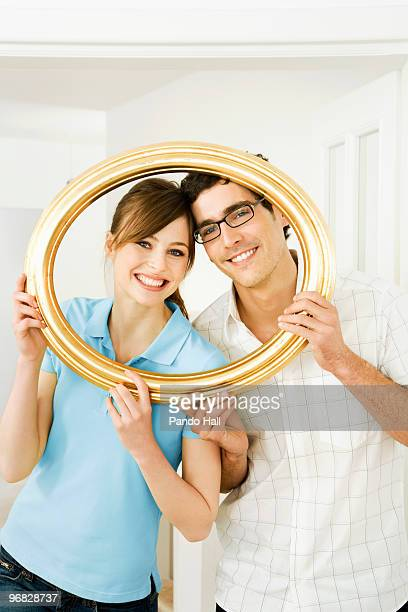 Young couple looking through frame, smiling